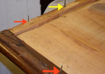 Comò a Lira. Rimosso il telaio del piano, freccia rossa chiodi industriali e gialla chiodo quadrato originale.