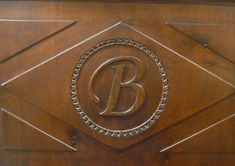 Storica Farmacia in Zogno Bg, pannello frontale del bancone con iniziali del Farmacista Mario Brighenti (inizio 1900).