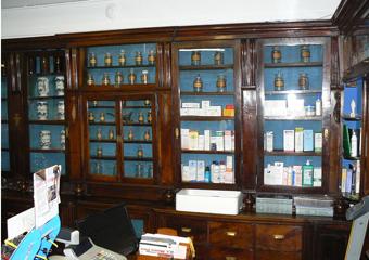 Storica Farmacia in Zogno Bg, la parete di arredi ora prima del restauro.
