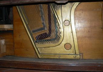 Pianoforte verticale a carica inizio 1900. Telaio in ghisa dove tensionate le corde musicali, visibili togliendo il pannello inferiore.