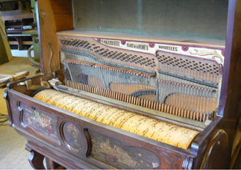 Pianoforte verticale a carica inizio 1900. In evidenza il rullo che attiva la meccanica dello strumento nell'esecuzione dei brani.