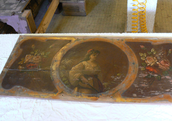 Pianoforte verticale a carica inizio 1900. Il pannello superiore dipinto presenta un'importante fenditura.