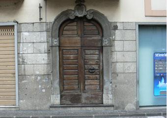 Portone in noce 1600, Portone prima del restauro contornato da portale in pietra con stemma Cavalleresco nella chiave di volta.