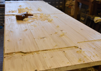 Portone in larice stile 700'. Realizzazione delle parti interne dei battenti in legno di abete come da tradizione, fase della piallatura a mano.