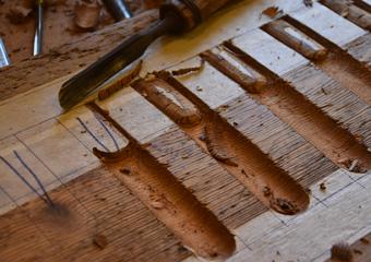 Portone in larice stile 700'. Decorazione posta al livello dei capitelli in pietra eseguita a mano.